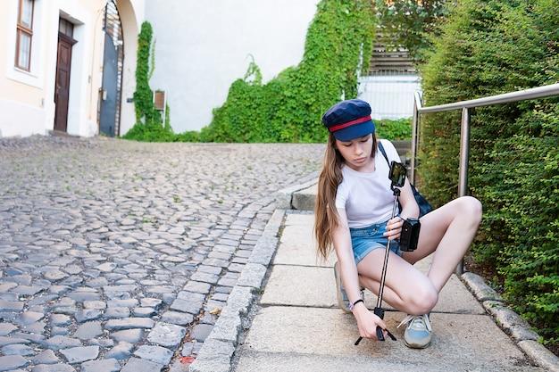 Uma garota com cabelos longos define um tripé com um telefone na rua. Foto Premium
