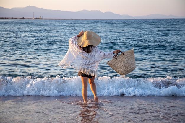Uma garota com um grande chapéu e uma bolsa de vime caminha ao longo da costa do mar. conceito de férias de verão. Foto gratuita