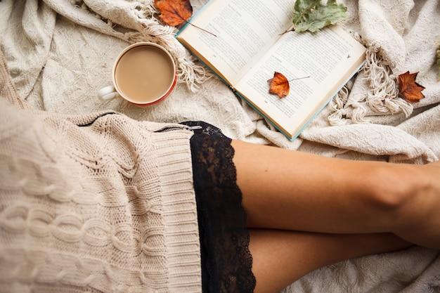 Uma garota com um suéter quente senta-se sobre um cobertor de lã bege e detém uma caneca de café quente nas mãos dela. Foto Premium