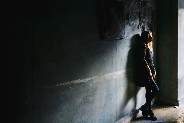 Uma garota com uma visão sonhadora se inclina para uma parede em um café Foto gratuita