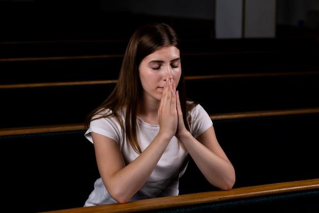 Uma garota cristã de camisa branca está sentado e orando com coração humilde na igreja Foto Premium