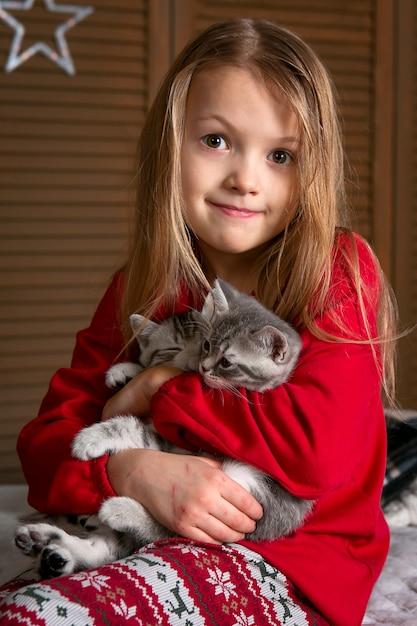 Uma garota de pijama vermelha está sentada na cama com gatinhos fofos. emoção brilhante. Foto Premium