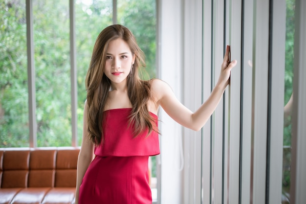 Uma garota de vestido vermelho está de pé ao lado da janela. Foto Premium
