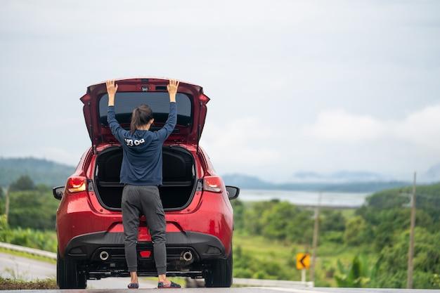 Uma garota de viagem e carro na estrada Foto Premium