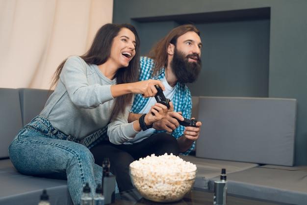 Uma garota e um cara jogam uma consola de jogos. Foto Premium
