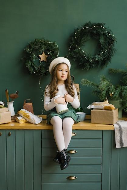 Uma garota elegante em uma boina branca senta-se em uma elegante cozinha decorada para o natal e o ano novo em esmeralda ou verde. guirlandas de natal na parede. a menina está segurando um jarro branco Foto Premium