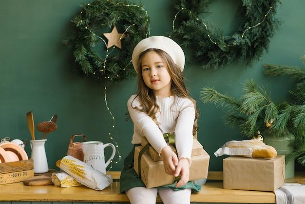 Uma garota elegante em uma boina branca senta-se em uma elegante cozinha decorada para o natal e o ano novo em esmeralda ou verde. guirlandas de natal na parede. menina segurando um presente de natal Foto Premium