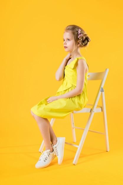 Uma garota está sentado em uma cadeira branca sobre um fundo amarelo. Foto Premium