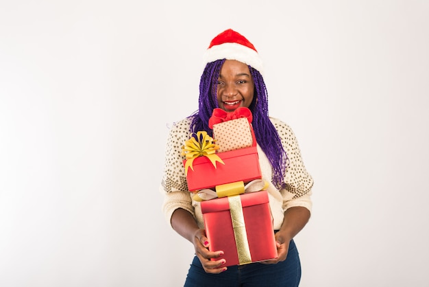 Uma garota feliz de pele escura tem muitos presentes vermelhos nas mãos. Foto Premium