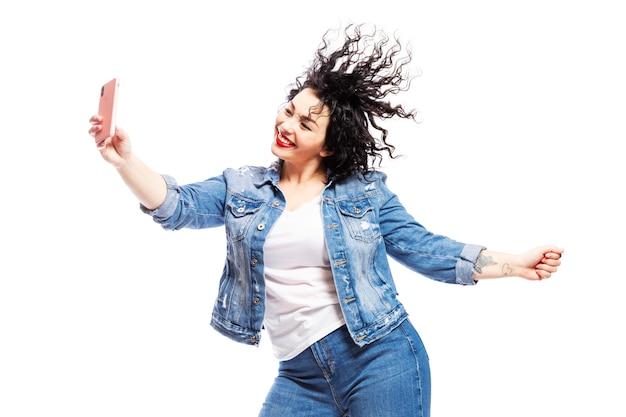 Uma garota que ri dançando olha para o telefone e tira uma selfie Foto Premium