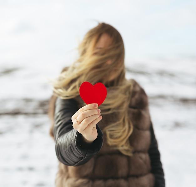 Uma garota segurando um coração vermelho na mão. Foto Premium