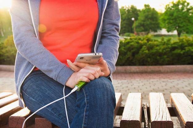 Uma garota usa um smartphone ao ar livre enquanto carrega de um banco de energia externo Foto Premium