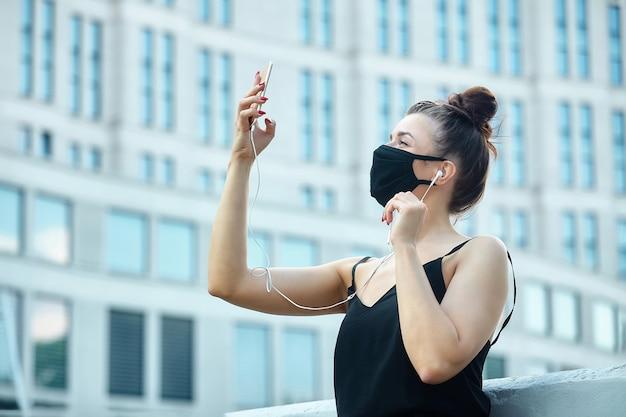 Uma garota usando uma máscara facial está tomando uma selfie Foto Premium