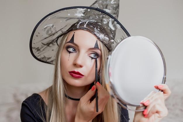 Uma garota vestida de bruxa faz para si uma maquiagem de halloween Foto Premium