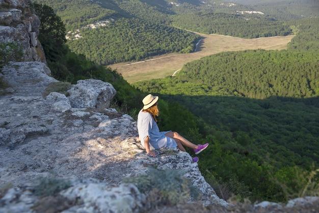 Uma garota viajante com um chapéu na cabeça dela se senta no topo de uma montanha Foto Premium