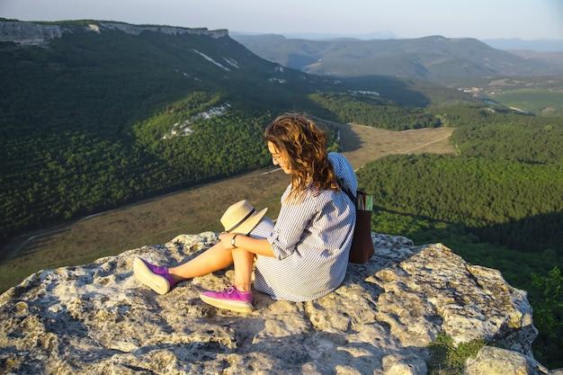 Uma garota viajante senta-se no topo de uma montanha e segura seu chapéu Foto Premium