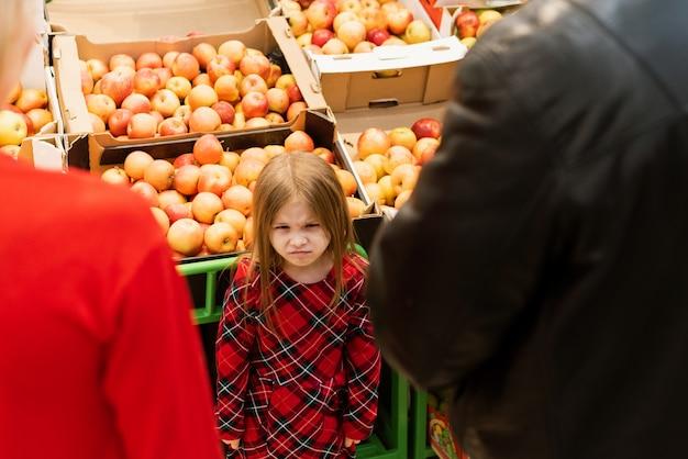 Uma garotinha de 5 anos parece mal com mamãe e papai. menina histérica chateada com os olhos fechados, chorando alto enquanto manipula os pais e fica contra barraca de comida no supermercado Foto Premium