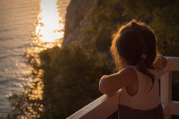 Uma garotinha na varanda com vista para o mar e o pôr do sol. Foto Premium