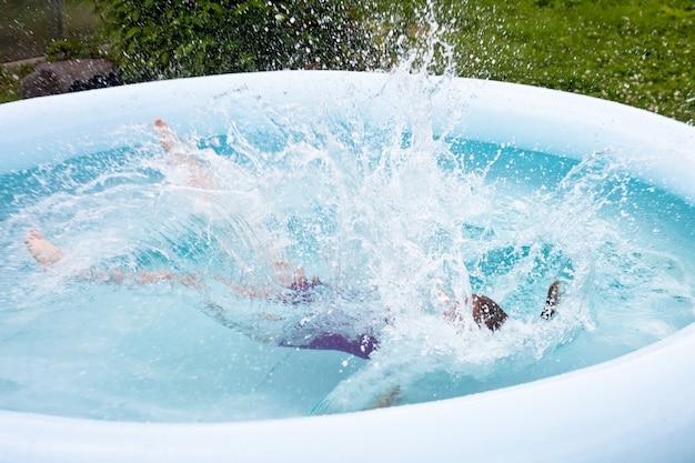 Uma garotinha pula na piscina. forte espirrando. Foto Premium