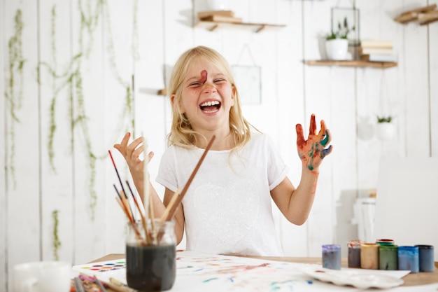 Uma garotinha rindo e encantadora, com cabelos loiros, sardas e olhos azuis bagunçou-se de tinta. criança criativa com tinta no rosto e mãos. Foto gratuita