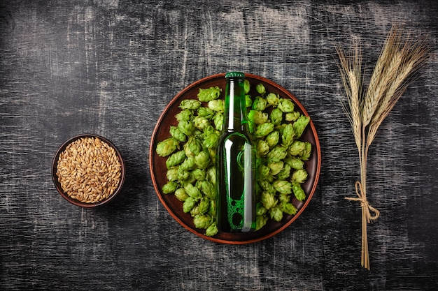 Uma garrafa de cerveja em um pulo verde em um prato com grãos e espigas de trigo no contexto Foto Premium