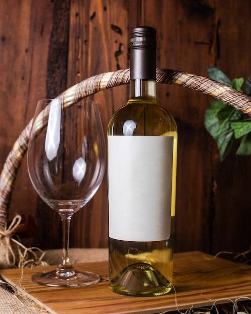 Uma garrafa de vinho branco vista frontal, juntamente com o copo vazio na mesa de madeira Foto gratuita