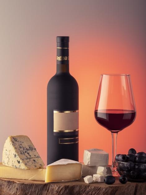 Uma garrafa de vinho, um copo de vinho tinto, queijo e uvas em uma mesa de madeira. Foto Premium