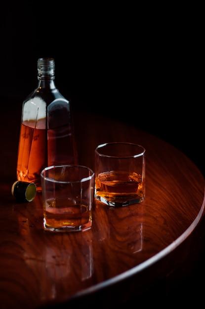 Uma garrafa e copos de licor na mesa de madeira Foto Premium
