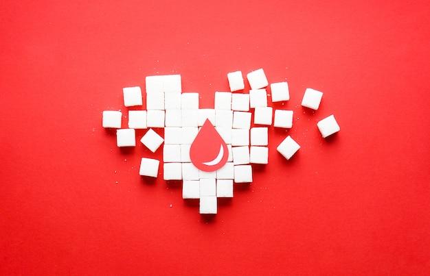 Uma gota de sangue em um coração feito de cubos de açúcar branco puro Foto Premium