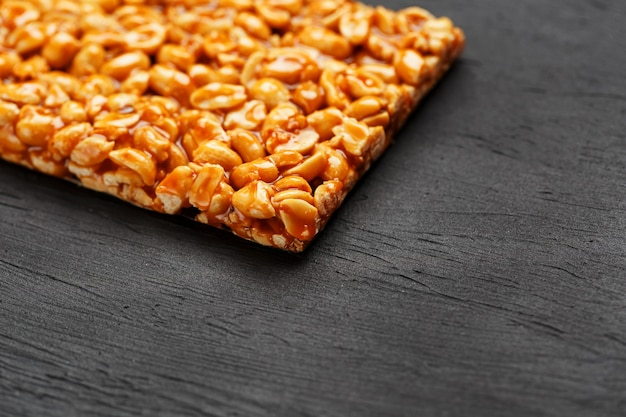 Uma grande telha dourada de amendoim, um bar em um melaço doce. kozinaki doces úteis e saborosos do oriente Foto Premium