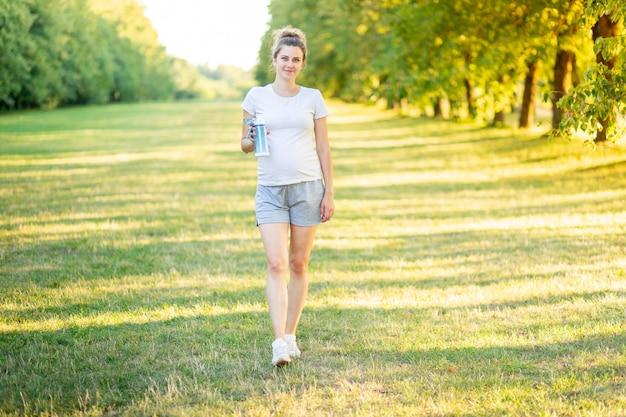 Uma grávida pratica esportes na natureza no verão e bebe água de uma garrafa Foto Premium