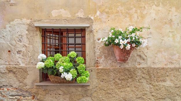 Uma janela aberta com treliça e flores no peitoril da janela. Foto Premium