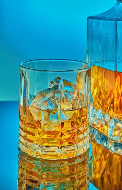 Uma jarra de cristal quadrada e de vidro com uísque escocês ou conhaque no fundo, sobre um fundo gradiente azul com reflexão Foto Premium