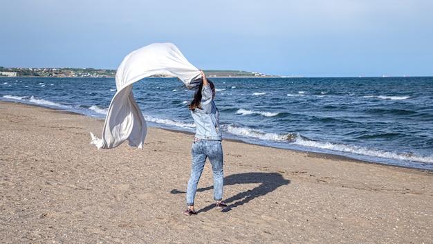 Uma jovem à beira-mar se diverte segurando um grande lençol ao vento, um estilo de vida livre. Foto gratuita
