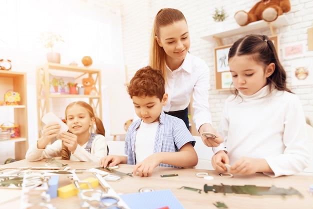 Uma jovem ajuda as crianças a dobrarem partes de cartolina. Foto Premium