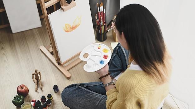 Uma jovem artista com uma paleta na mão, pintando na tela, enquanto está sentada no chão de sua oficina. Foto Premium