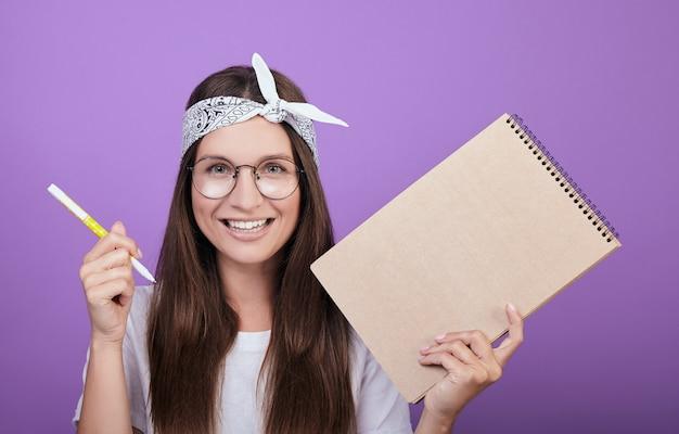 Uma jovem artista segura um álbum e uma caneta nas mãos. Foto Premium