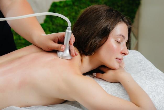 Uma jovem bonita está desfrutando de uma massagem profissional a vácuo no spa. cuidados com o corpo. salão de beleza. Foto Premium