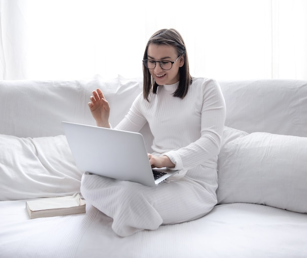 Uma jovem bonita está sentada em casa em um sofá branco com um vestido branco e trabalhando em um laptop. Foto gratuita