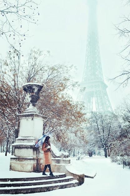 Uma jovem caminha em um inverno nevado paris contra a torre eiffel Foto Premium