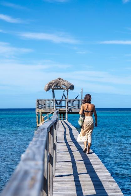 Uma jovem caminhando ao longo da praia de sandy bay em roatan island. honduras Foto Premium