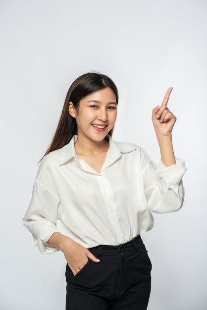 Uma jovem com uma camisa branca e apontando para cima Foto gratuita