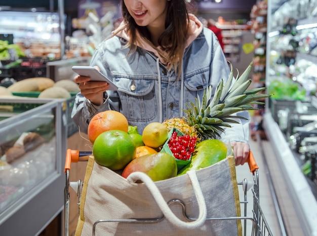 Uma jovem compra mantimentos em um supermercado com um telefone nas mãos. Foto gratuita