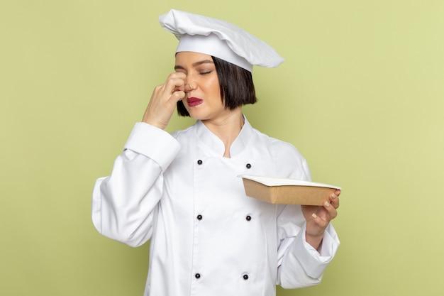 Uma jovem cozinheira de frente para um cozinheiro com um terno branco e boné segurando um pacote fechando o nariz na parede verde Foto gratuita