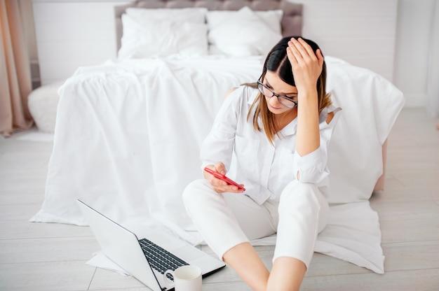 Uma jovem de 25 anos de aparência européia senta-se perto de uma cama com um telefone na mão em casa. sente dor de cabeça ou fadiga ocular, más notícias Foto Premium