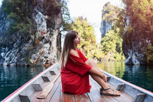 Uma jovem de biquíni está sentada em um pequeno barco perto de uma ilha tropical. férias de verão. Foto gratuita