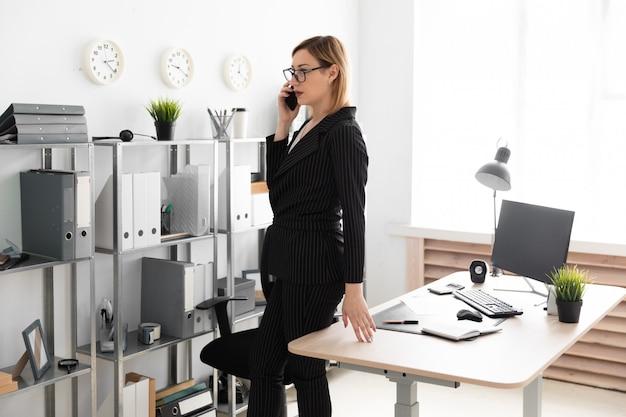 Uma jovem de pé no escritório e falando ao telefone. Foto Premium