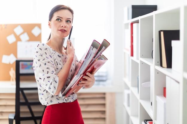 Uma jovem de pé no escritório, falando no telefone e segurando uma pasta com documentos. Foto Premium