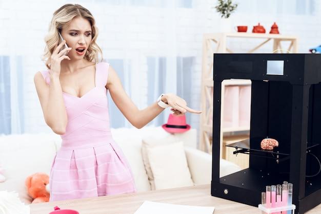 Uma jovem e linda garota está experimentando com uma impressora 3d. Foto Premium