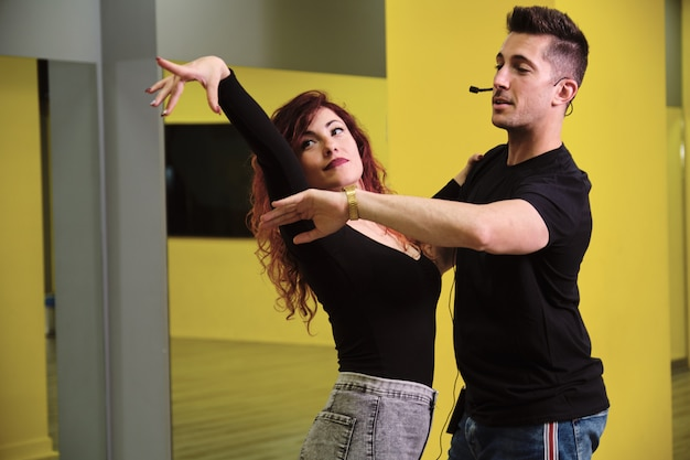 Uma jovem e um homem ensinando salsa e bachata Foto Premium